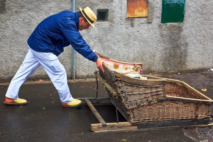 Direkt vor dem Eingang des tropischen Gartens in Monte startet eine beliebte Touristenattraktion: eine traditionelle Korbschlittenfahrt über das Kopfsteinpflaster, Madeira, Portugal - © sarra22 / Shutterstock