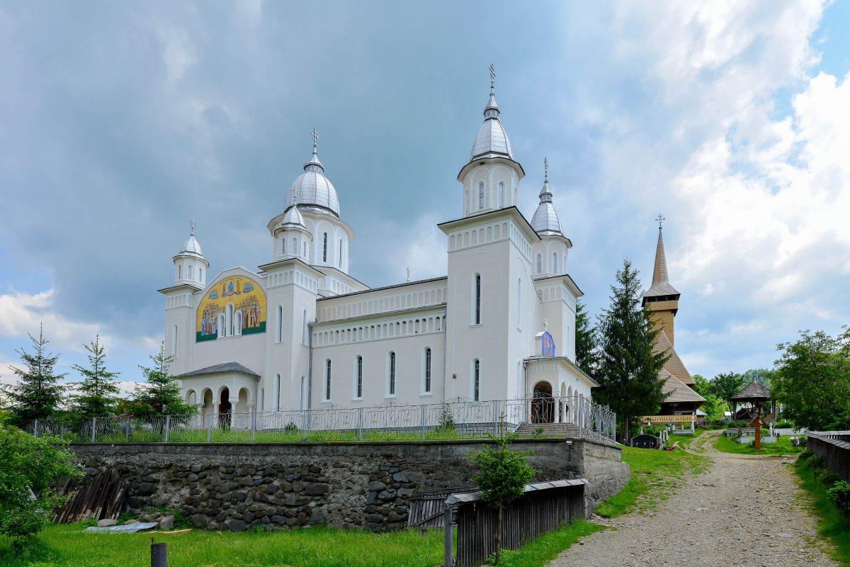 Gleich neben der traditionellen Holzkirche von Botiza bildet die moderne Allerheiligenkirche einen starken Kontrast, Rumänien - © FRASHO / franks-travelbox