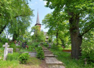 Mit ihrem charakteristischen spitzen Dach thront die berühmte Holzkirche von Deseşti auf einem idyllischen Hügel mitten in der Ortschaft, Rumänien - © FRASHO / franks-travelbox
