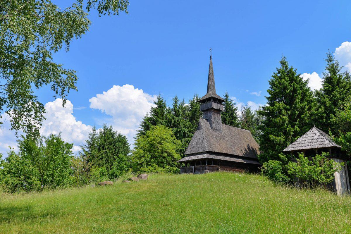 Auf einem Hügel im Museumsdorf thront die traditionelle Holzkirche von Oncesti aus dem 16. Jahrhundert, Sighetu Marmatiei, Rumänien - © FRASHO / franks-travelbox