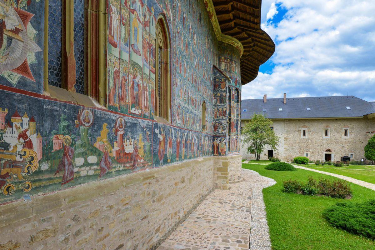 Mit dem Grün des Gartens und dem Blau des Himmels ergibt der Bilderteppich auf der Kirchenfassade von Sucevița ein überwältigendes Fotomotiv, Rumänien - © FRASHO / franks-travelbox