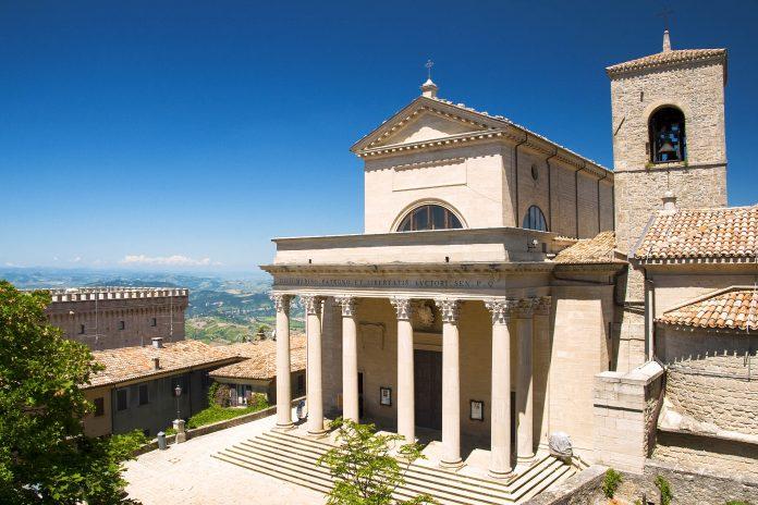 Eingangsfront der Basilica del Santo in Città di San Marino, daneben der Turm der Chiesetta San Pietro - © Pablo Debat / Shutterstock