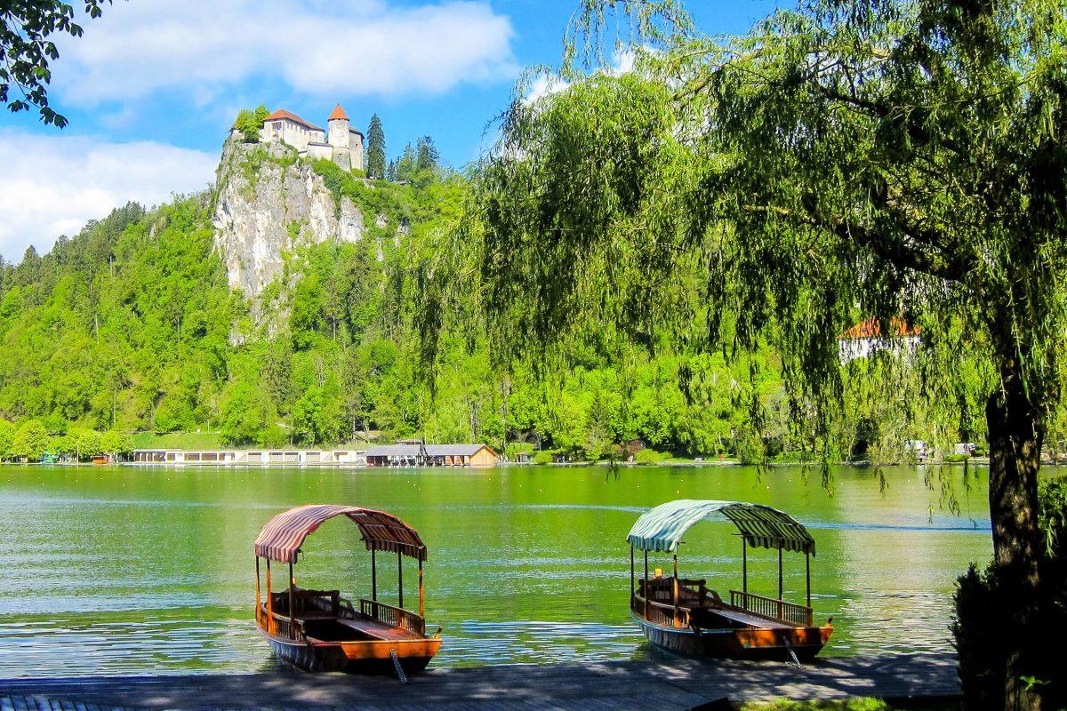 Am Ufer des Bleder Sees in Slowenien dümpeln Ausflugsboote, die Touristen über die stille Wasseroberfläche bringen - © FRASHO / franks-travelbox