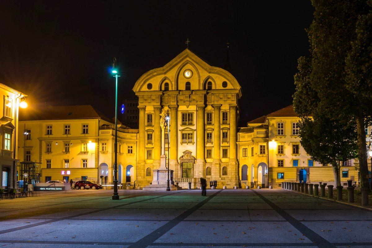 Ihre unverwechselbare Fassade und der markante Giebel machen die Dreifaltigkeitskirche zu einem der meistfotografierten Bauwerke von Ljubljana, Slowenien - © trabantos / Shutterstock