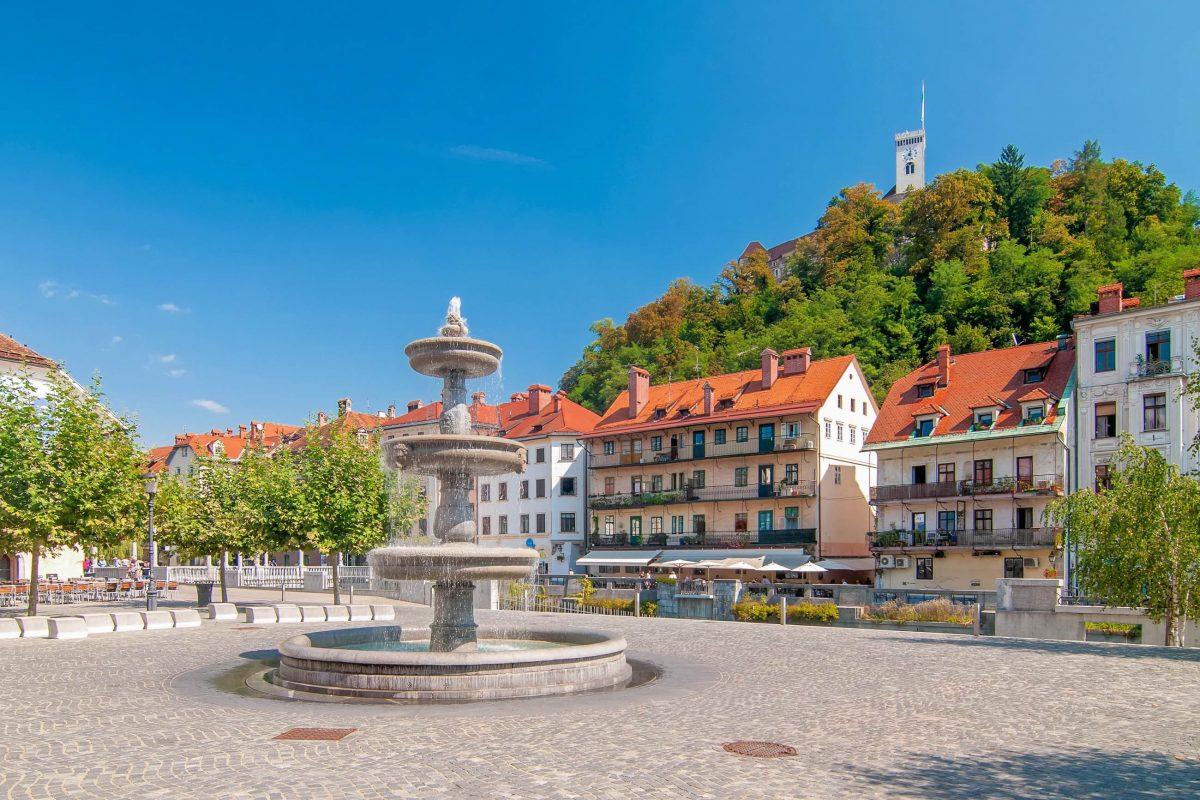 Mit einem zentralen Brunnen geschmückt bietet der Novi Trg einen herrlichen Blick auf die Burg von Ljubljana, Slowenien - © Soru Epotok / Shutterstock