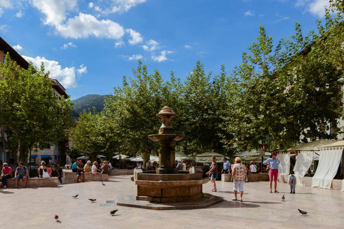 Am von Platanen beschatteten Plaça Constitució vor der Kirche spielt sich das Leben in Sóller ab, Mallorca, Spanien - © James Camel / franks-travelbox