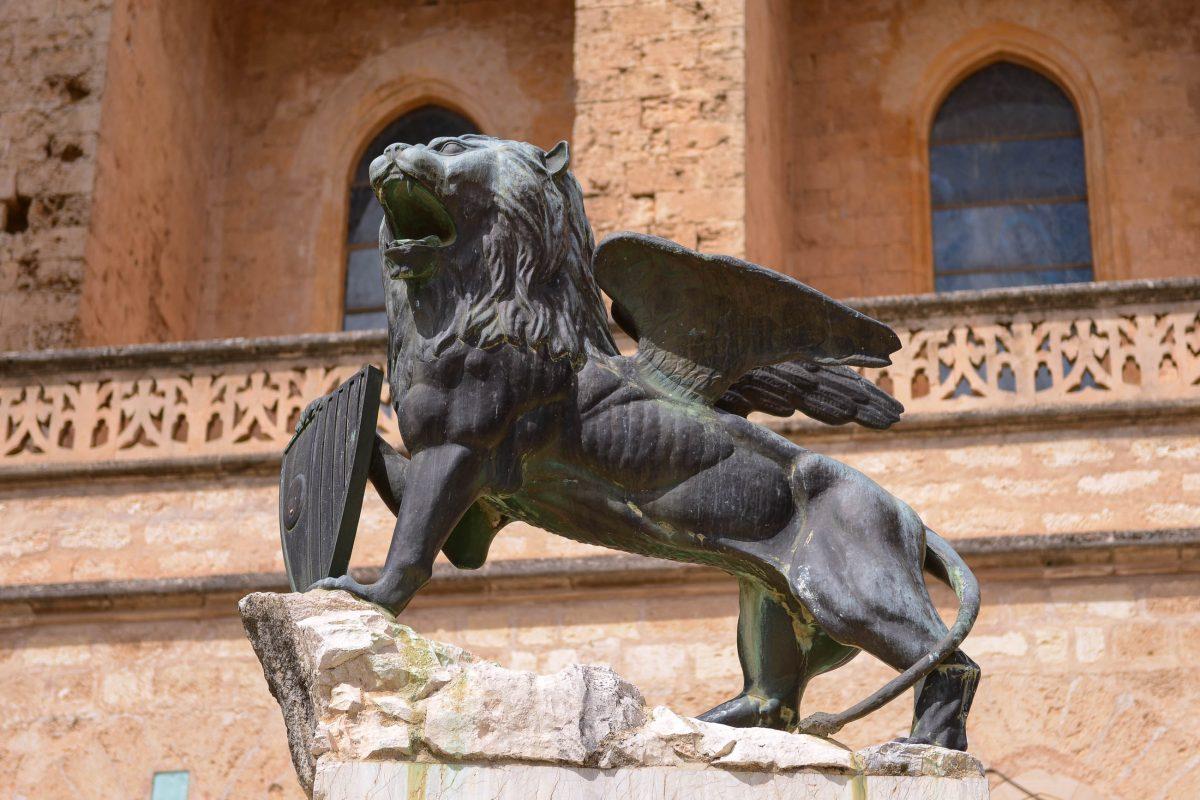 """Auf dem Kirchenvorplatz thront der geflügelte Bronzelöwe """"Lleó de Sant Marc"""" zu Ehren des Heiligen Markus, Stadtpatron von Sineu, Mallorca, Spanien - © James Camel / franks-travelbox"""