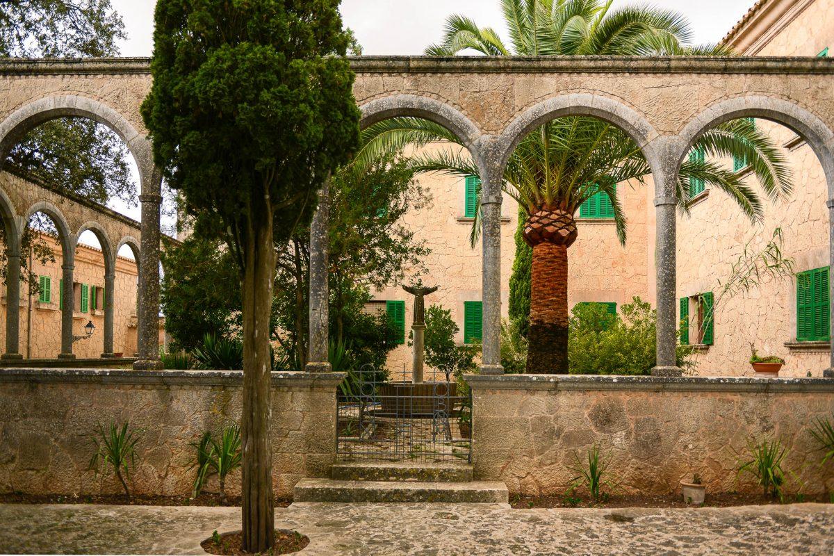 Der Innenhof des Santuari de Nostra Senyora de Cura am Klosterberg Randa ist mit Palmen und Figuren idyllisch gestaltet, Mallorca, Spanien - © James Camel / franks-travelbox