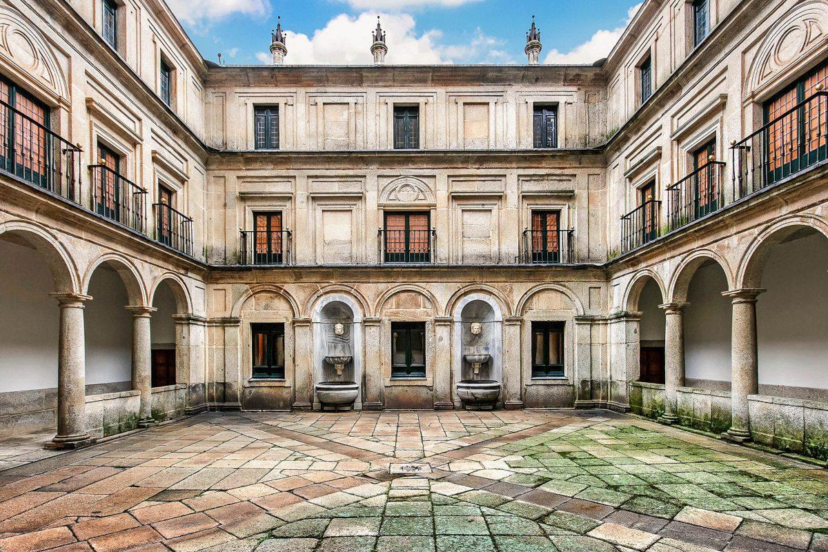 "Der berühmte Innenhof ""Patio de los Mascarones"" im Palast El Escorial in San Lorenzo, Spanien - © canadastock / Shutterstock"