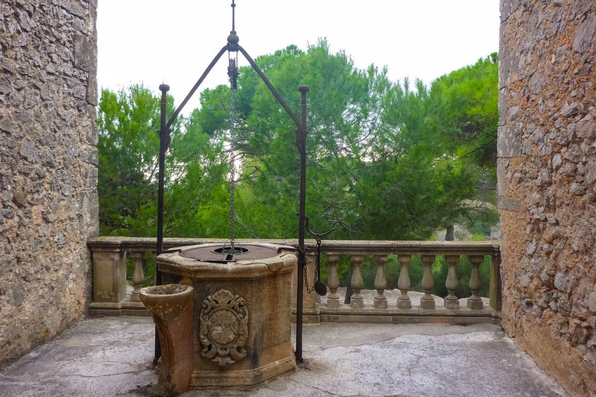 In einer Nische des Santuari de Monti Sion ruht vor einem spektakulären Panorama ein alter Ziehbrunnen, Mallorca, Spanien - © Lila Pharao / franks-travelbox