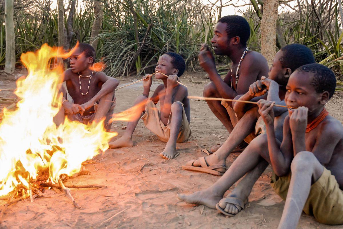 Eine Gruppe Buschmänner des Hadzabe-Stammes sitzt am Feuer in der Nähe des Lake Eyasi in Tansania - © pcruciatti / Shutterstock