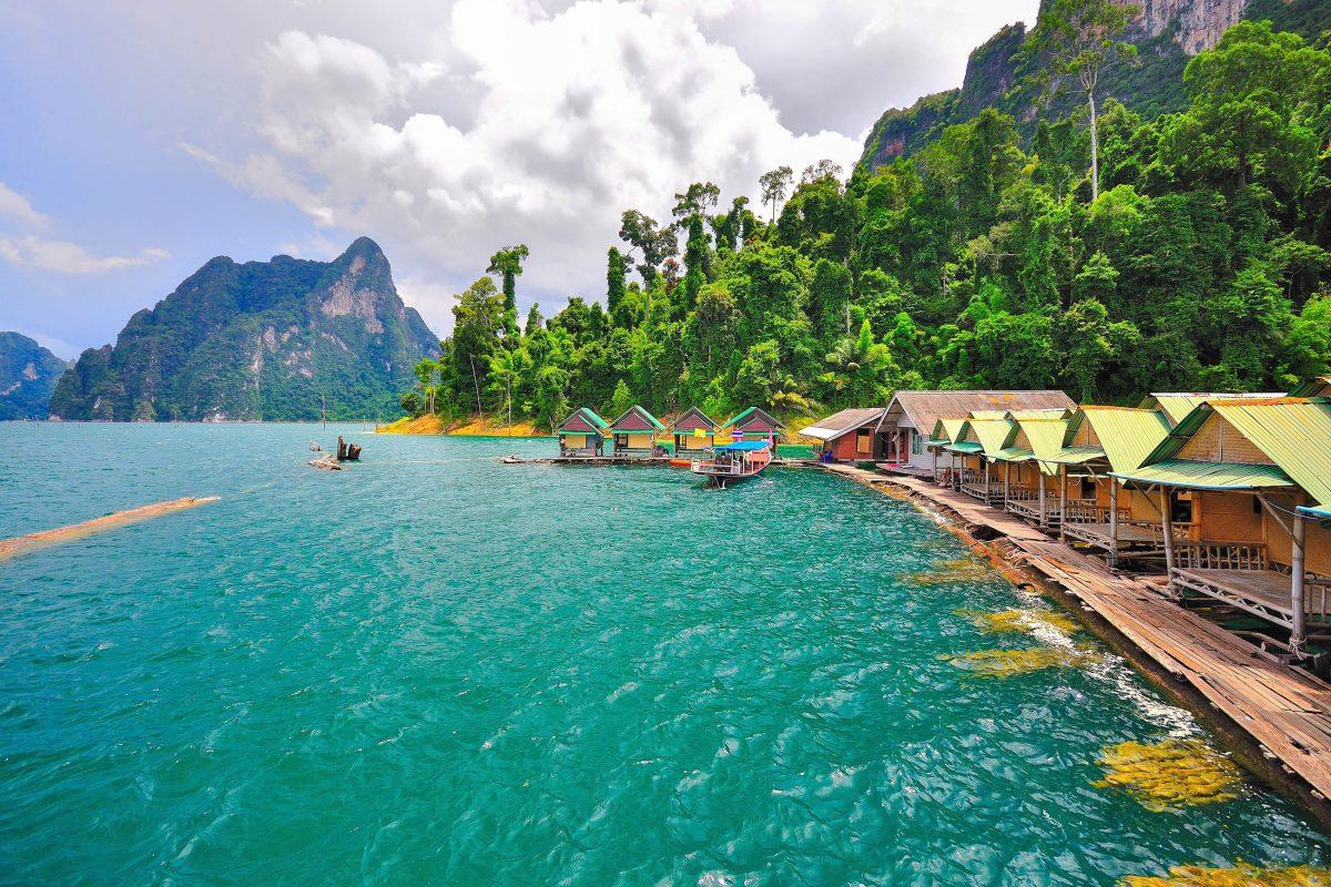 Mit dem Langboot werden Besucher auf dem malerischen Chiao Lan See im Khao Sok Nationalpark zu den schwimmenden Häusern der Einheimischen transportiert, Thailand - © ability riddle / Shutterstock