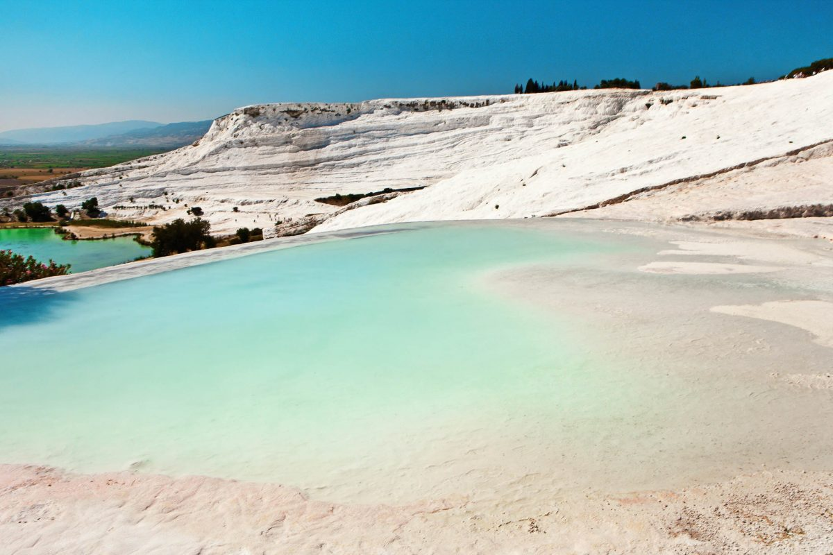 Die Kalksinterterrassen von Pamukkale im Südwesten der Türkei sind in eine traumhafte Landschaft eingebettet - © eleana / Shutterstock