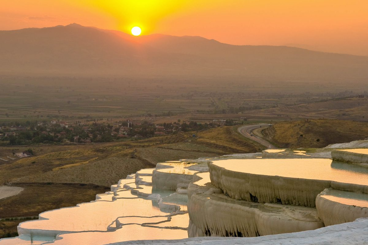 Die Sonne schickt ihre letzten Strahlen auf die glitzernden Pools von Pamukkale, Türkei - © Erhan Dayi / Shutterstock