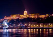 Der hell erleuchtete Burgpalast in Budapest bei Nacht mit der Kettenbrücke im Vordergrund, Ungarn - © James Camel / franks-travelbox