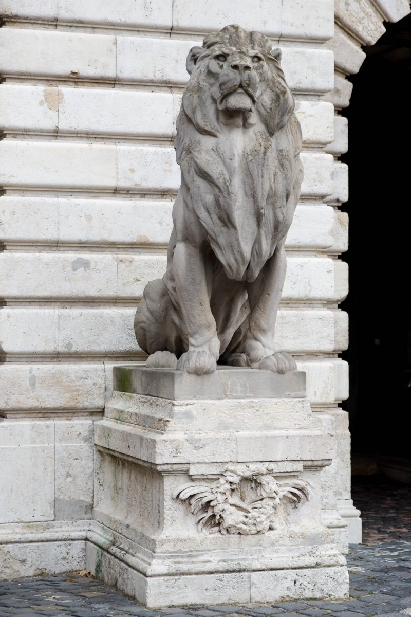 Zwei steinerne Löwen mit strengem Blick bewachen das Löwentor, das in den Innenhof des Burgpalastes von Budapest führt, Ungarn - © James Camel / franks-travelbox