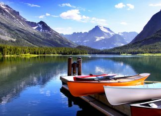 Bunte Kanus warten am McDonald Lake im Glacier Nationalpark auf einen Bootsausflug, Montana, USA - © SNEHIT / Shutterstock