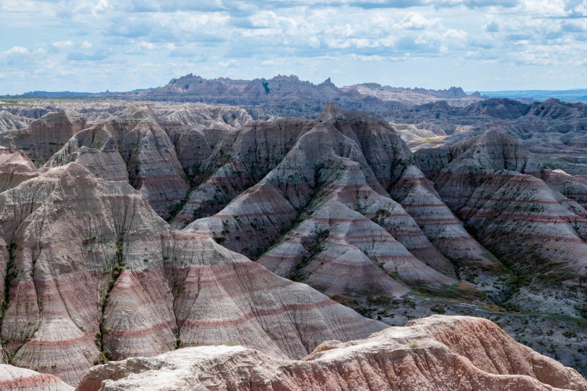Die unterschiedlichen Gesteinsschichten der schroffen Landschaft in den Badlands präsentieren sich von rot über ocker bis braun und grau, South Dakota, USA - © James Camel / franks-travelbox