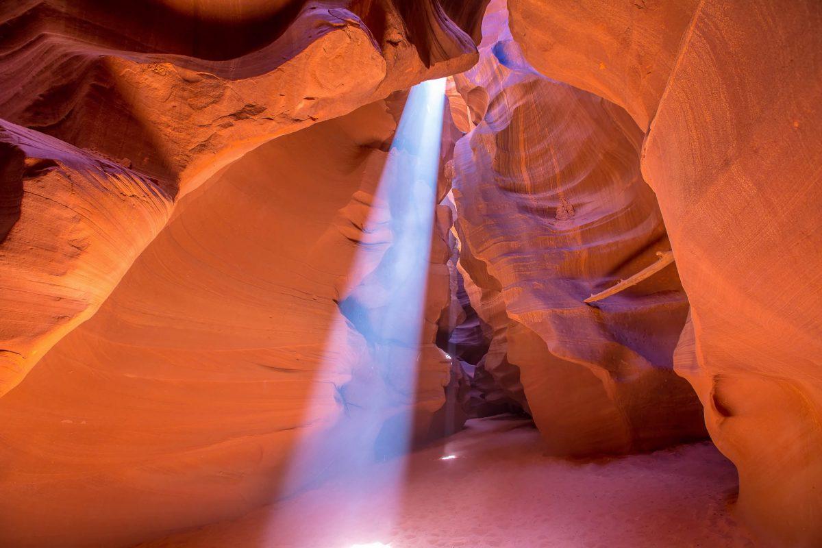 Zu Mittag fallen die Sonnenstrahlen im Antelope Canyon bis auf den Boden der atemberaubenden Schlucht, USA - © holbox / Shutterstock