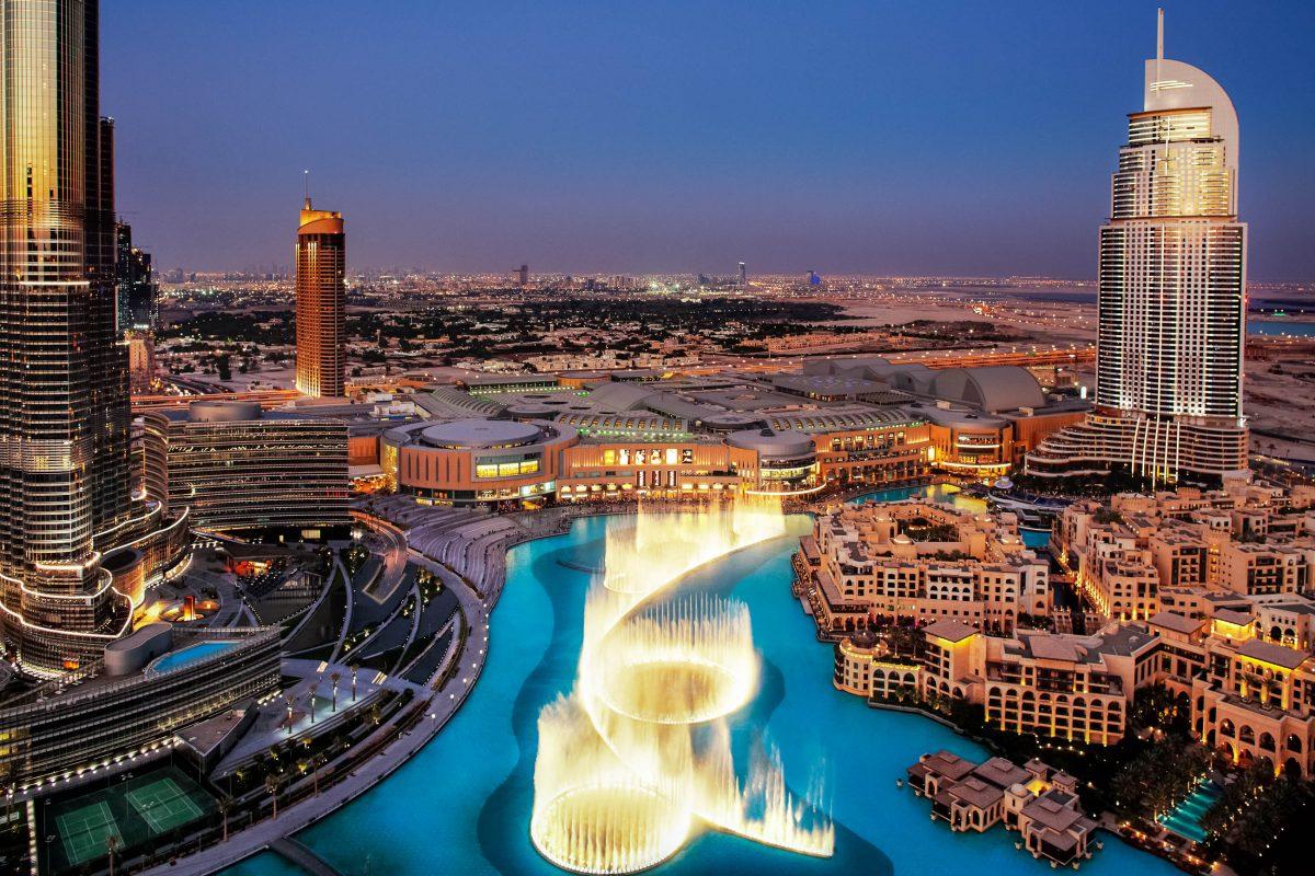 Blick auf den Dubai Lake mit der nächtlich beleuchteten Dubai-Fountain, links im Bild der Wolkenkratzer Burj Khalifa, VAE - © Sophie James / Shutterstock