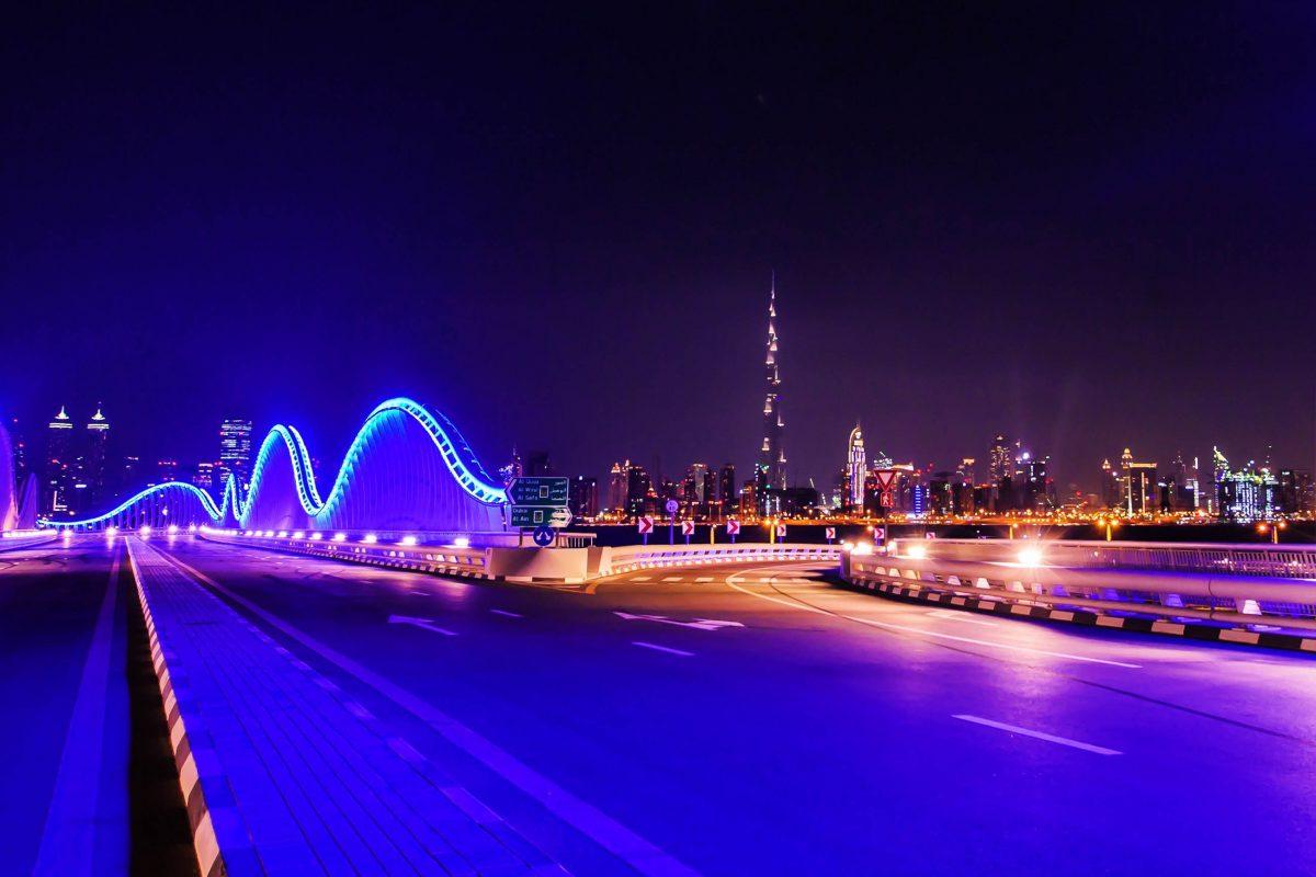 Blick auf die nächtlich beleuchtete Meydan Rennstrecke mit der Skyline von Dubai im Hintergrund, VAE - © Rus S / Shutterstock