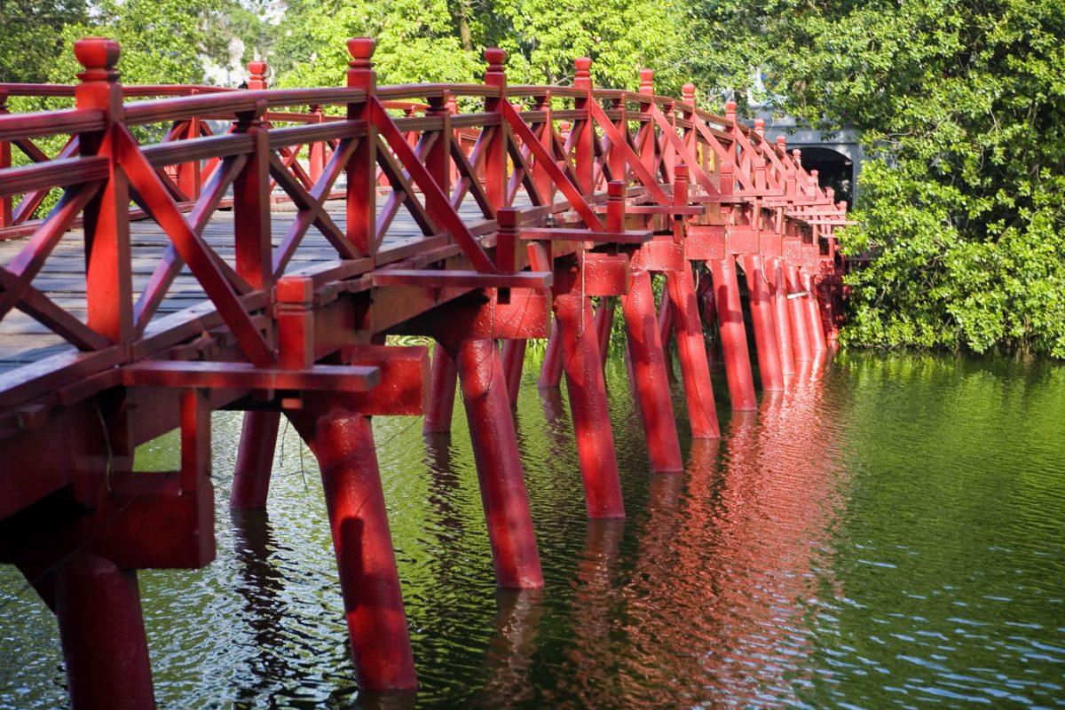 """The Huc-Brücke am Gelände des Jadeberg-Tempels wird auch als """"Rote Brück der aufgehenden Sonne"""" bezeichnet, Hanoi, Vietnam - © Muellek Josef / Shutterstock"""