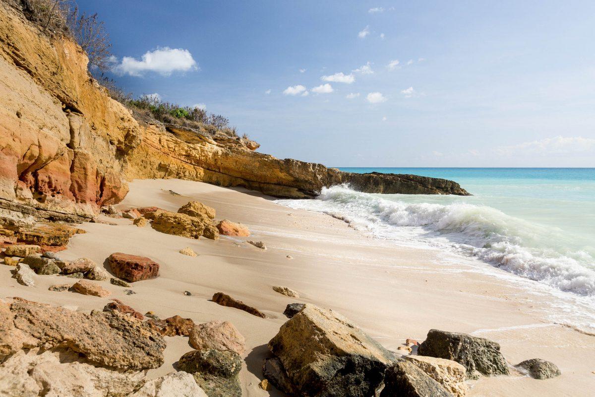 Der traumhafte Sandstrand von Cupecoy Bay beeindruckt durch seine Steilküsten, Höhlen und Felsformationen, die beinahe senkrecht hinter dem feinen Sandstreifen aufragen, Sint Maarten - © Steve Heap / Shutterstock