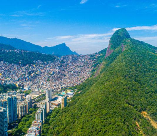 Luftaufnahme der Favela da Rocinha, dem größten Slum Brasiliens auf einem Berg in Rio de Janeiro, im Vordergrund die Skyline der Stadt - © Brastock / Shutterstock