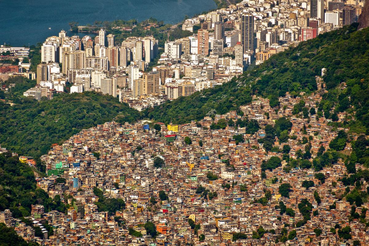 Luftbild der Favela da Rocinha am Hang in Rio de Janeiro, dahinter die Skyline der Stadt, Brasilien - © Donatas Dabravolskas / Shutterstock