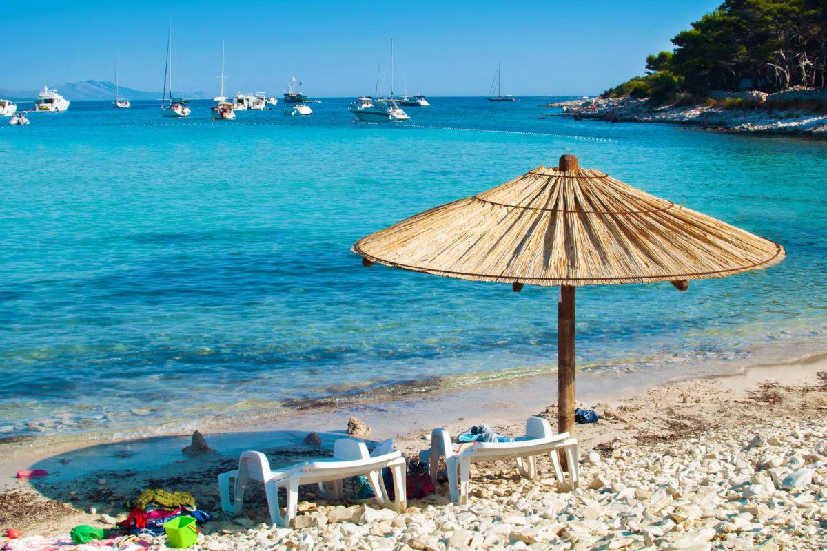 Sonnenschirm und Liegestühle am Kieselsandstrand von Dugi Otok. In der azurblauen Meereslagune ankern einige Yachten, Kroatien - © Shinedawn / Shutterstock