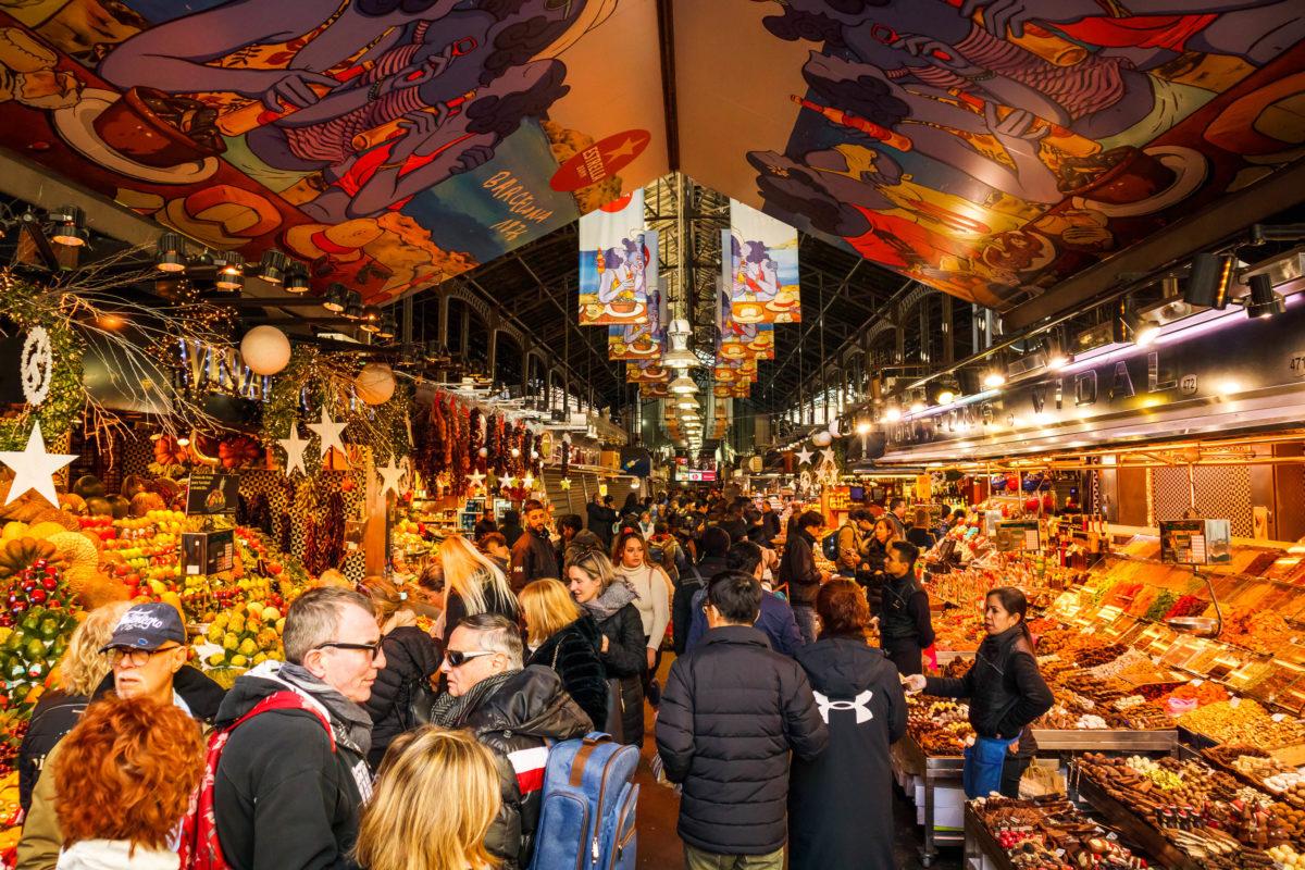Im Mercat de la Boqueria erledigen Einheimische ihren Wocheneinkauf und Touristen lassen sich im turbulenten Getümmel treiben, Barcelona, Spanien - © John Gress Media Inc / Shutterstock