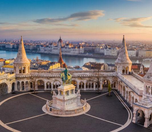 Die berühmte Fischerbastei in Budapest bei Sonnenaufgang mit der Statue von König Stephen I. und des ungarischen Parlaments im Hintergrund, Ungarn - © ZGPhotography / Shutterstock