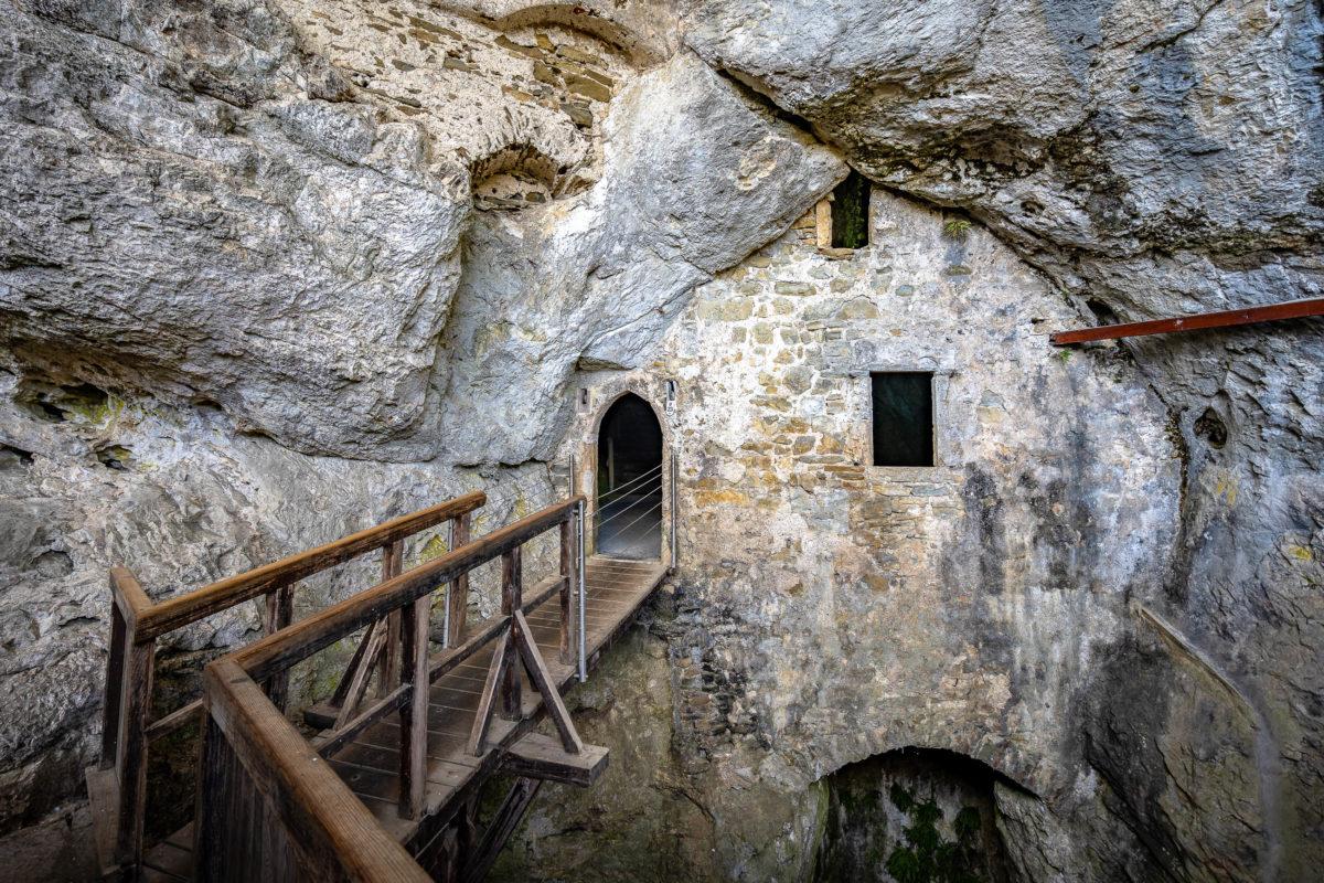 Die Besucher können sich ein Stück in die Höhlen der Burg Predjama vorwagen, in die sich die Burgherren bei Gefahr zurückziehen konnten, Slowenien - © Alex Cimbal / Shutterstock