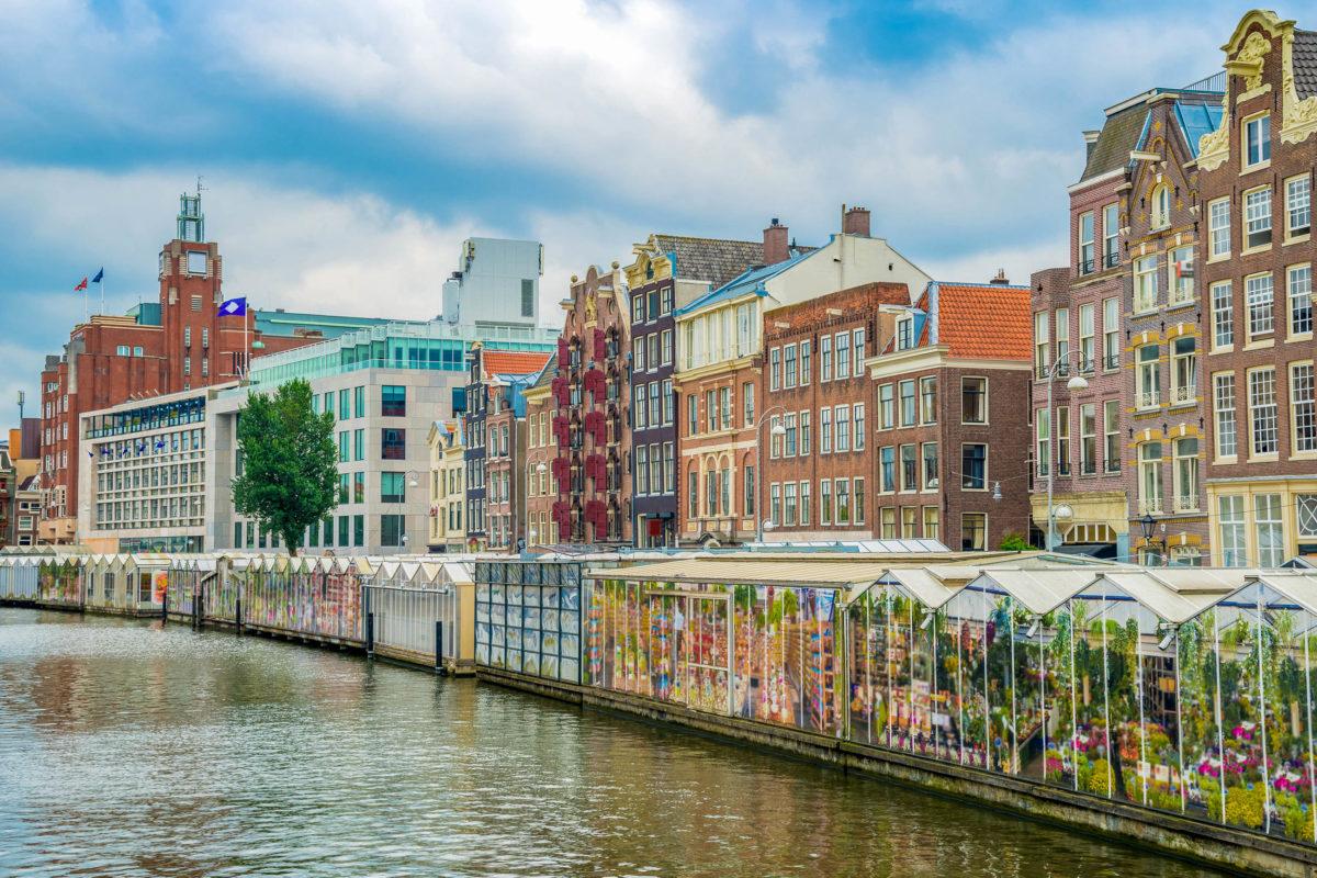 """Der """"Bloemenmarkt"""" (Blumenmarkt) ist ein schwimmender Markt an der Singel-Gracht mitten im Herzen des Grachtengürtels von Amsterdam, Niederlande - © NaughtyNut / Shutterstock"""