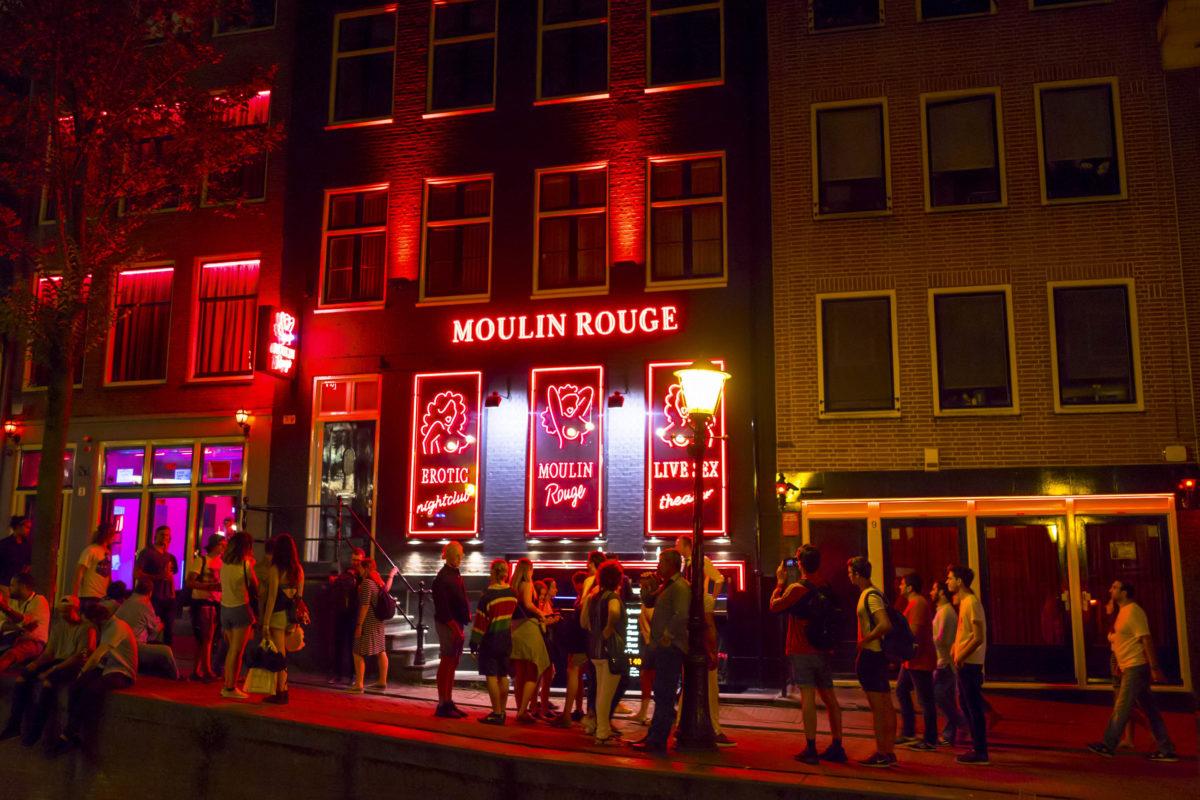 """Im Rotlichtviertel """"De Wallen"""" in Amsterdam reiht sich ein Bordell an das nächste, die leicht bekleideten Damen räkeln hinter rot erleuchteten Schaufenstern, Niederlande - © 4kclips / Shutterstock"""