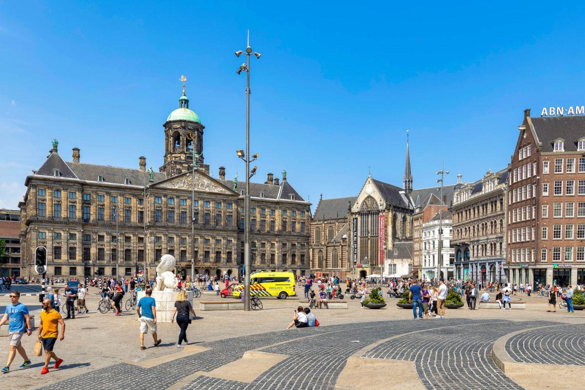 Mitten in der Innenstadt von Amsterdam liegt der vielbevölkerte Dam Platz mit dem imposanten Königspalast, Niederlande - © Laszlo Szirtesi / Shutterstock