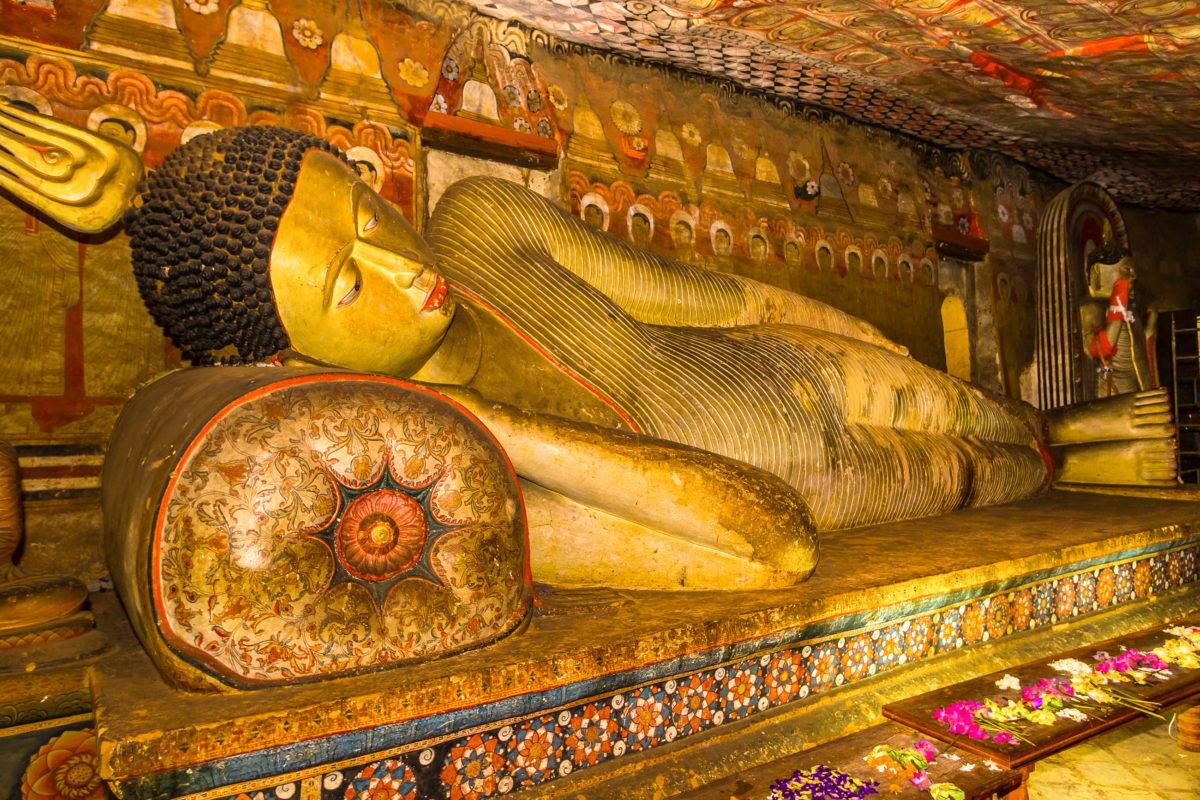 """In der """"Höhle des göttlichen Königs"""" befindet sich eine direkt aus dem Stein gehauene 14m lange liegende Buddha-Statue, Sri Lanka - © Nila Newsom / Shutterstock"""