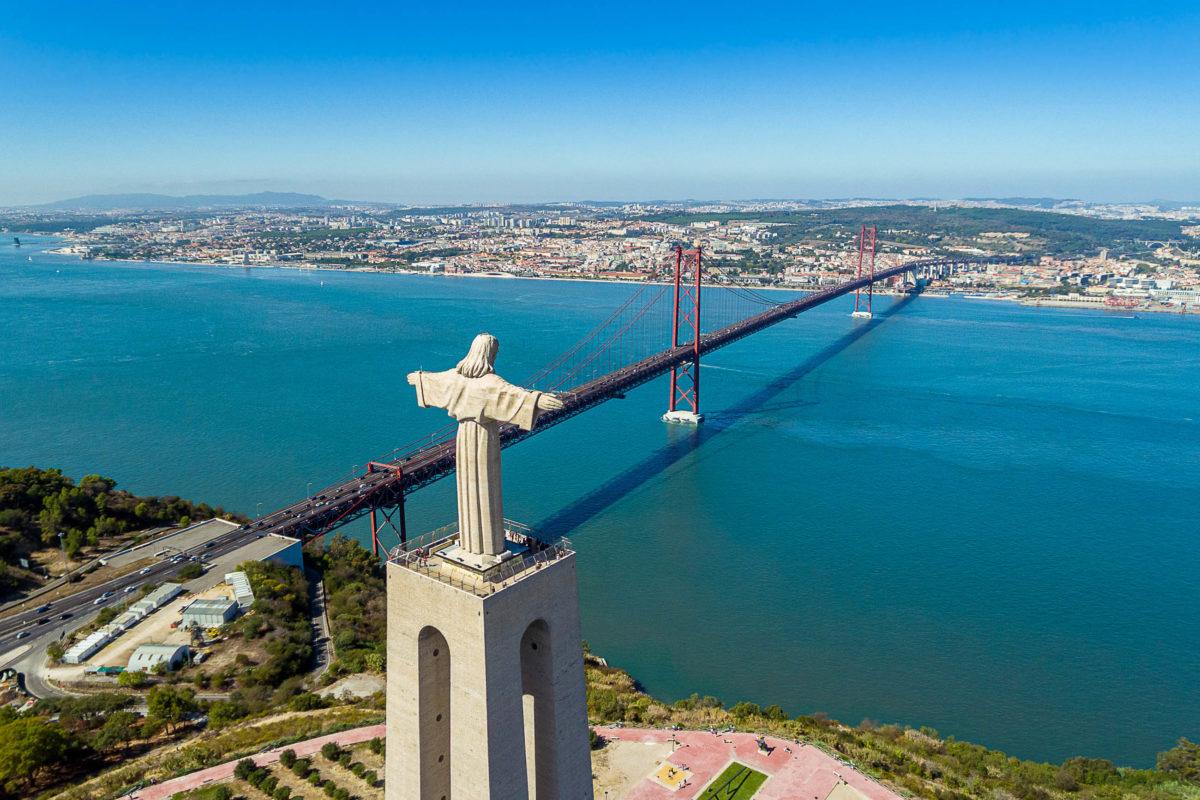 Die Christo Rei Statue bietet einen sensationellen Blick über Lissabon und die Ponte 25 de Abril, die über den Tejo führt, Portugal - © Sergio Sergo / Shutterstock