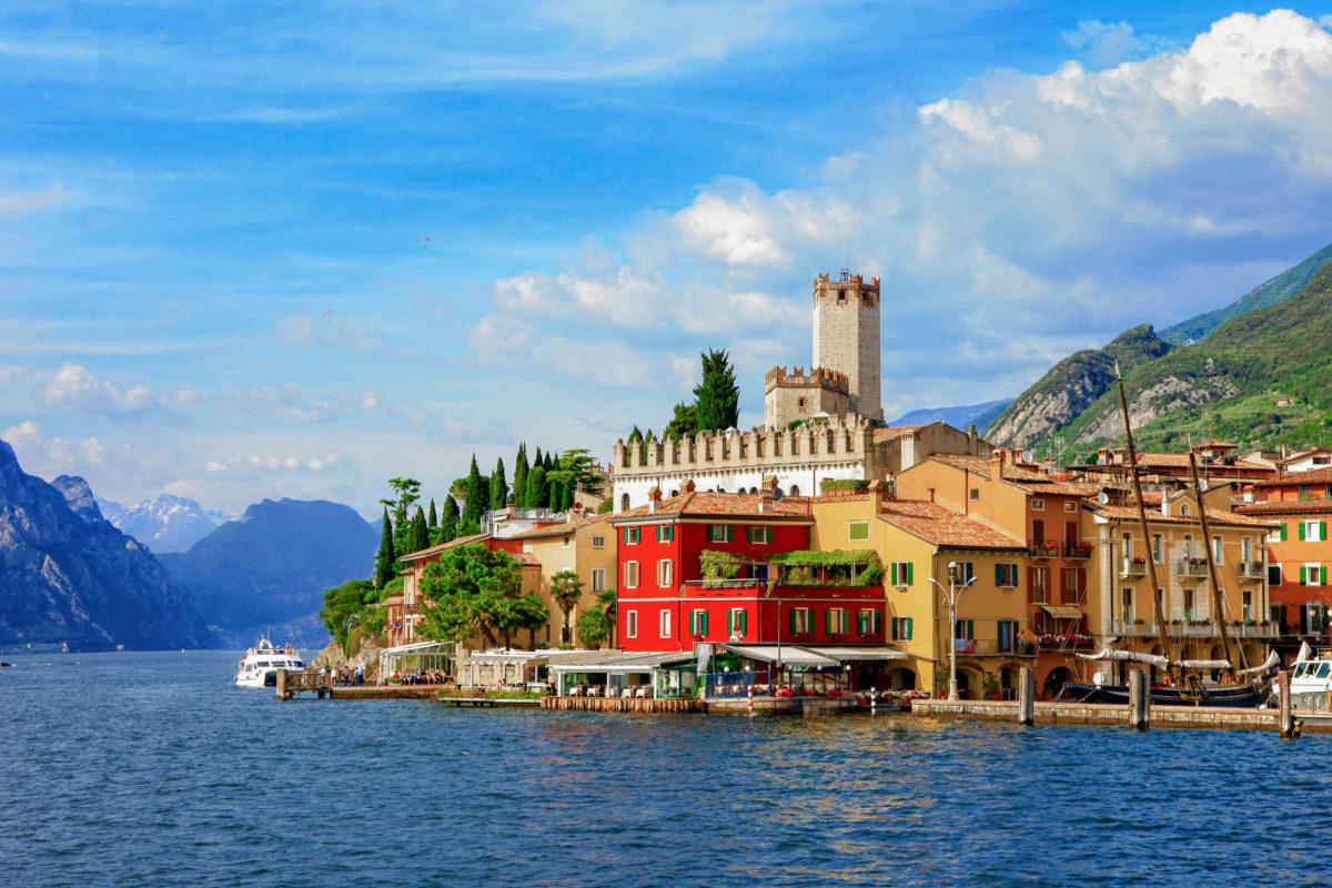 Sonnenanbeter, Windsurfer und Segler kommen am östlichen Ufer des Gardasees nach Malcesine, Italien - © leoks / Shutterstock