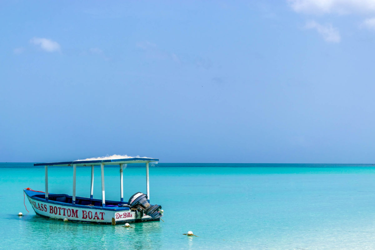 Ein  Glasboden-Motorboot angedockt am Seven Mile Beach auf Jamaika - © Debbie Ann Powell / Shutterstock