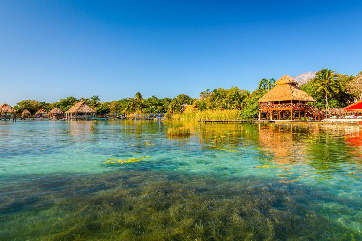 Das kristallklare Wasser und der weiße Sandboden des Sees lassen die Wasserfarben in verschiedenen türkisfarbenen und blauen Farbtönen erscheinen, Lagune Bacalar, Mexiko - © Paulo Miguel Costa / Shutterstock